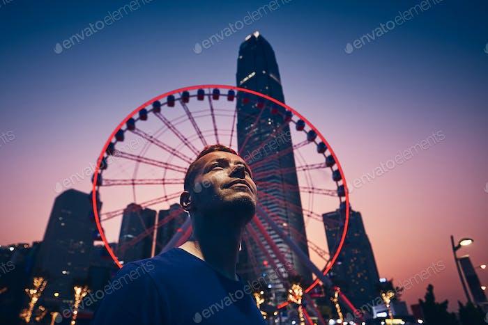 Nachtleben in Hongkong. Junger Mann (Reisende) gegen Riesenrad und städtische Skyline.