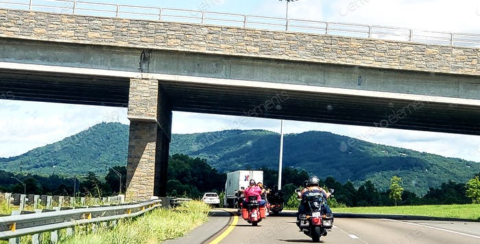 Automobile following motorcycle riders under a bridge headed for mountain getaway and vacation.