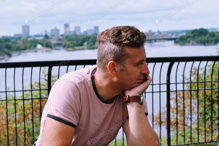 A man is sitting on a park bench deep in thought, contemplating
