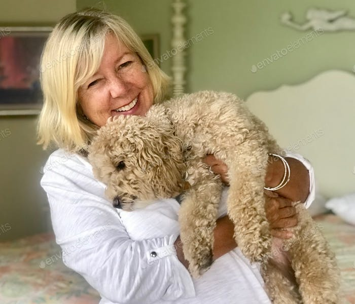 A baby boomer woman smiles with a cuddly golden doodle dog and pet