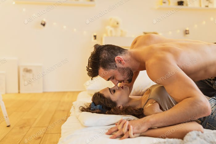 Beautiful passionate young couple hugging on the bed at home. Photo has a copy space for text