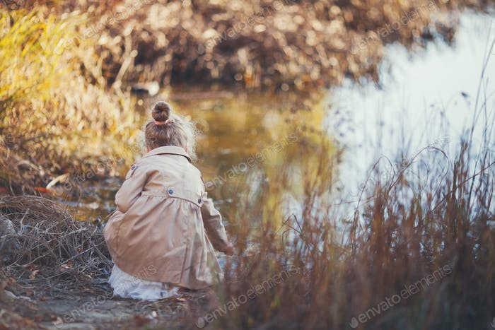 a girl in a beige cloak sits near the water among the reeds and autumn leaves