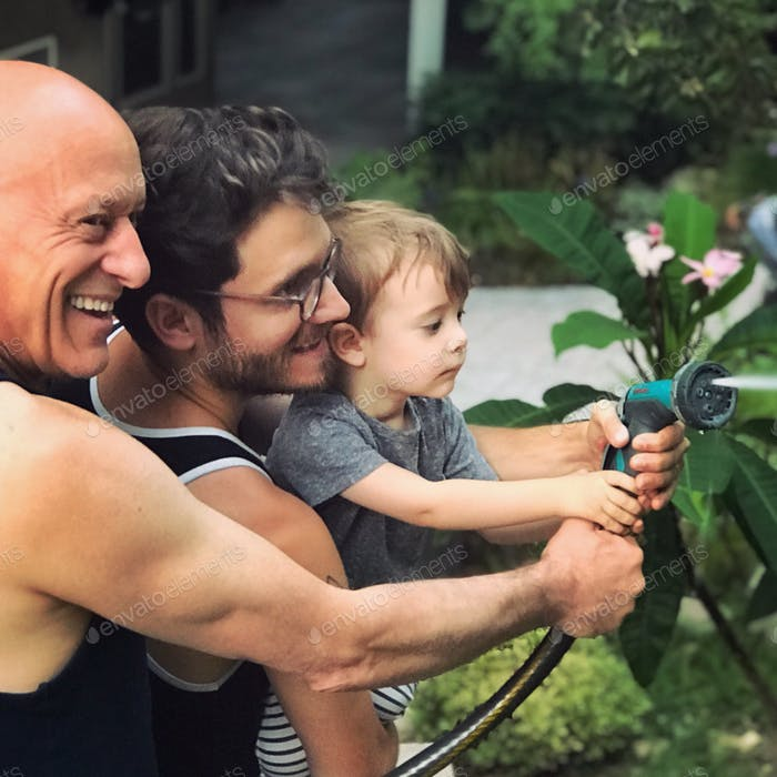 Three generations. Grandfather, son and grandson holding a hose and watering the garden