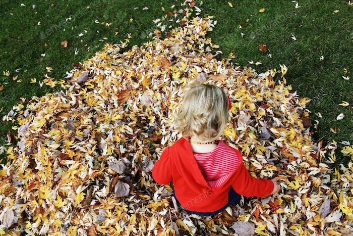 Toddler girl jumping in leaf pile
