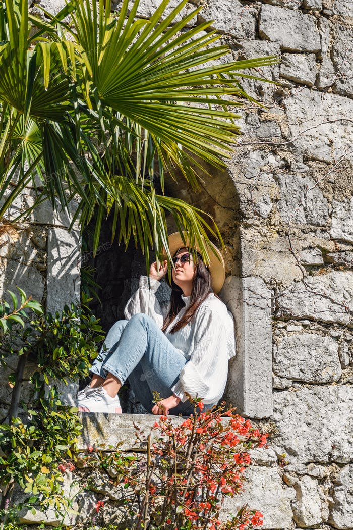 Beautiful young woman sitting inside a window of an old stone building in mediterranean gardens in