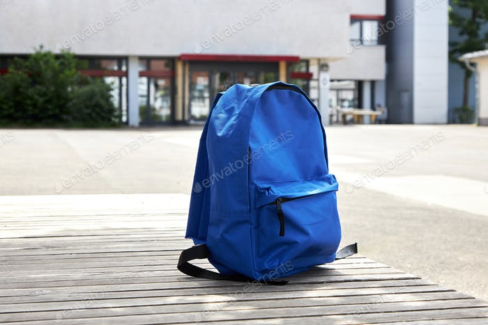 School background. Backpack on a bench