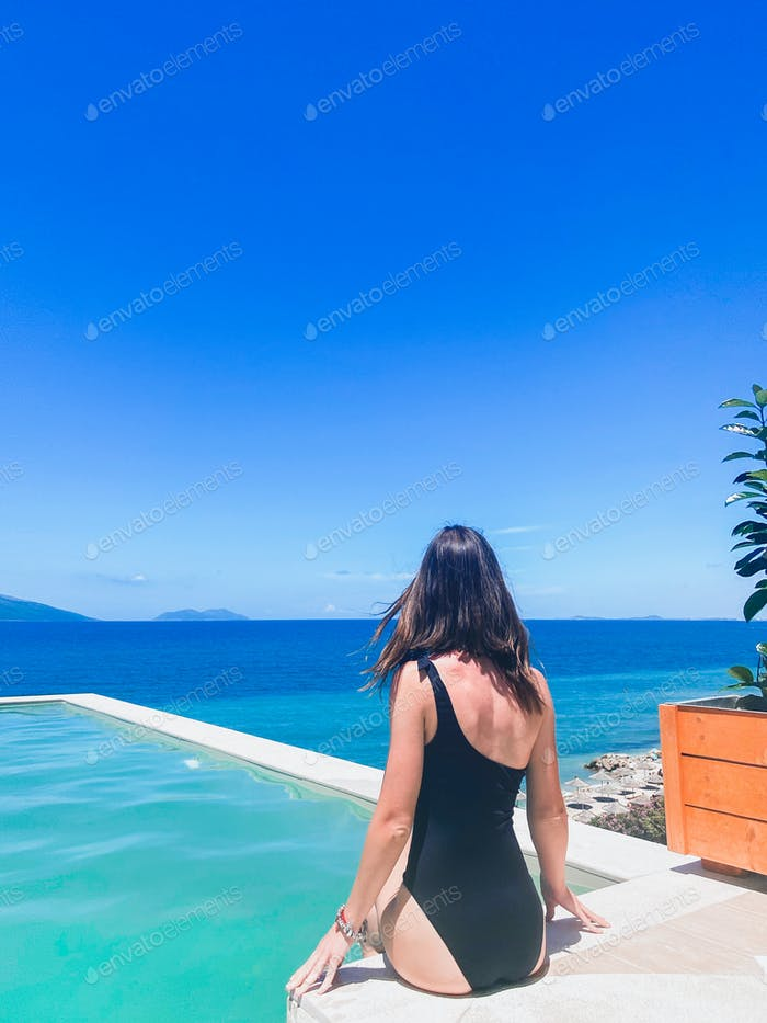 Woman enjoying summer vacation at the pool with sea view