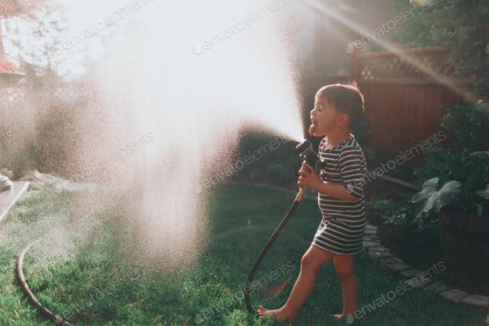 A little boy playing in the hose at sunset.