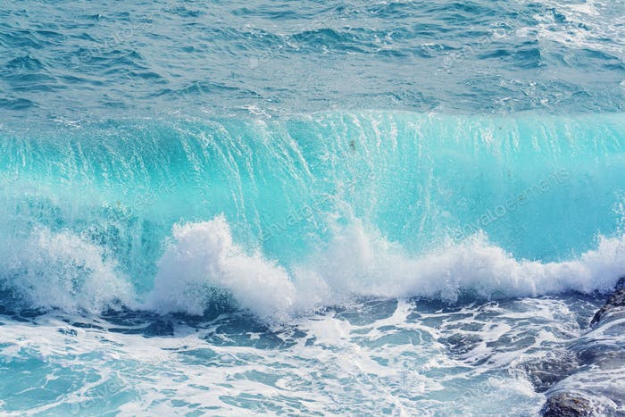 Closeup view of beautiful blue aquamarine rolling waves with splash and foam