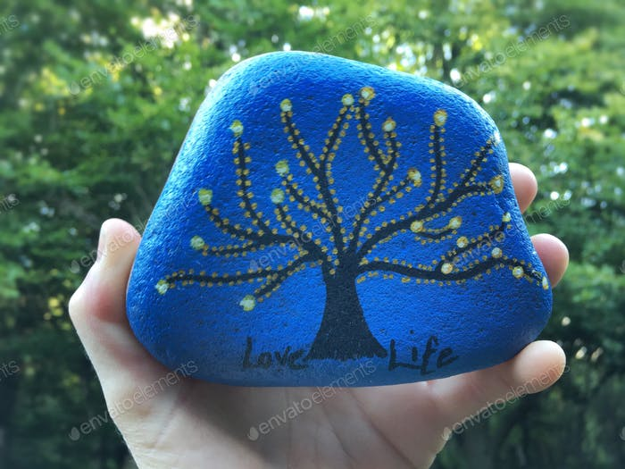 Positive message hand painted on a stone.