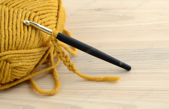 crochet hook and yellow wool on table