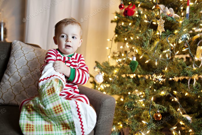 toddler in Christmas pajamas by a Christmas tree