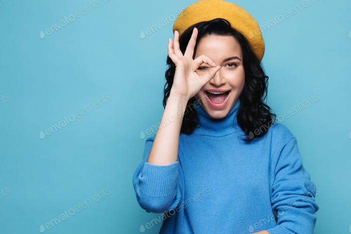 Smiling brunette woman showing okay sign intrigued look through circle wear yellow beret