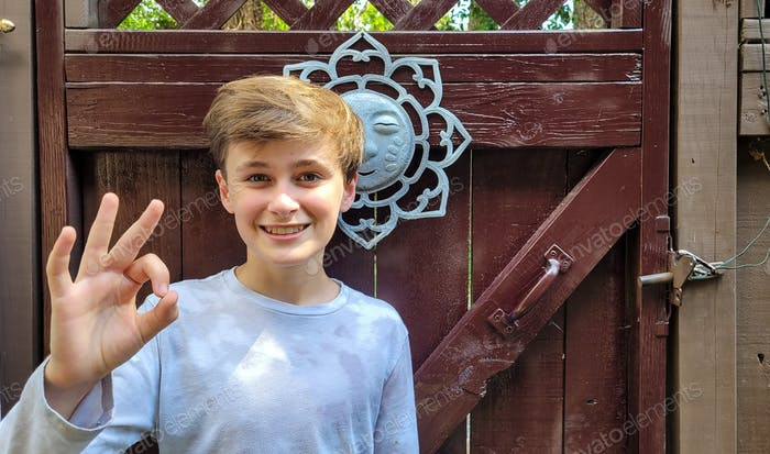 Ornamental wood door to gate is background for kid in the backyard happy and excited about future.