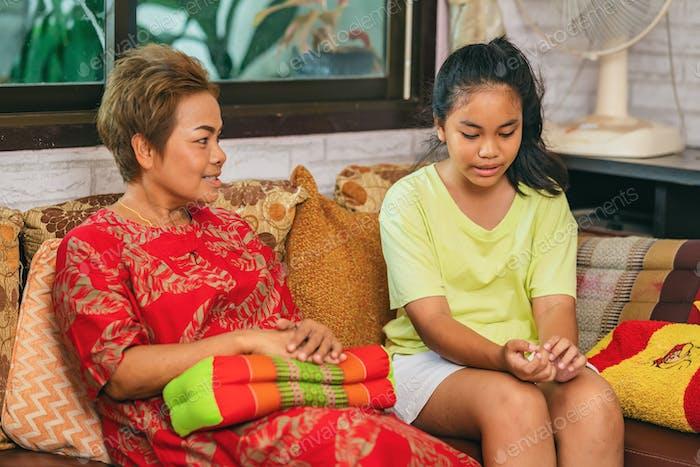 Feliz madre hablando con su hija y sentada en el sofá en casa en Tailandia.