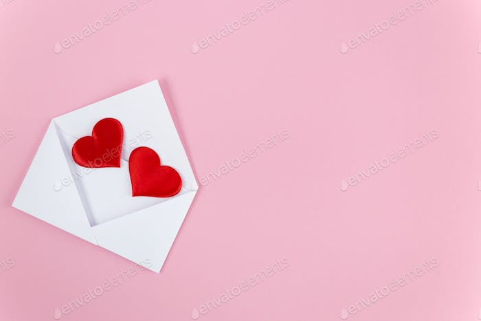 two red hearts fall out of a white envelope lying on a pink background