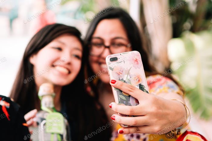 Two friends celebrating and taking a selfie with a smart phone.