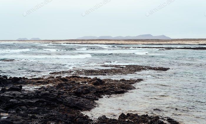 Vista panorámica del mar con playa rocosa contra el cielo en Fuerteventura, Islas Canarias.