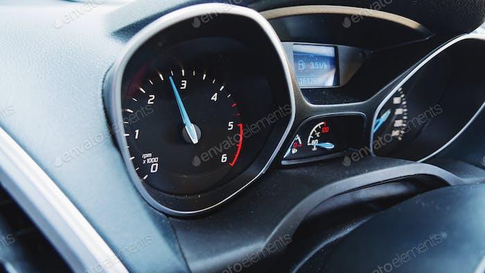 Car dashboard, car gauges, speedometer, rpm, black car interior. Driving a Ford car.