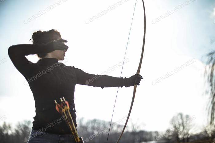 Woman practicing archery shooting arrows as a new hobby in her free time
