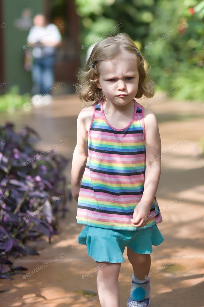 Angry toddler girl walking away in a huff outdoors on a bright sunny summer day