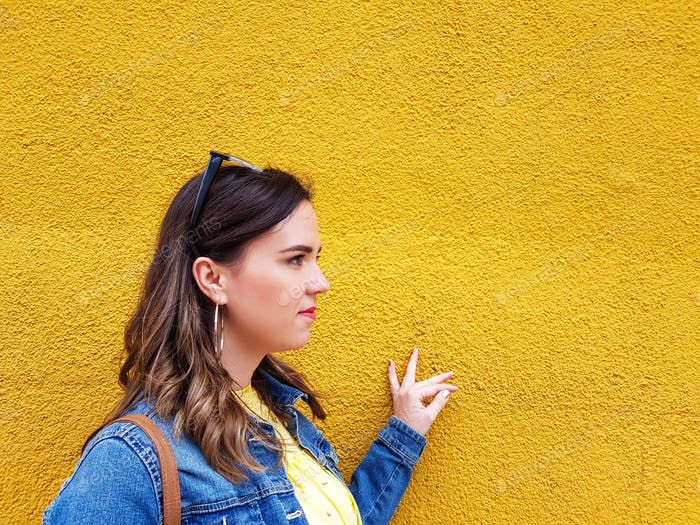 A minimalist shot of a young millenial woman on a yellow monochrome background.