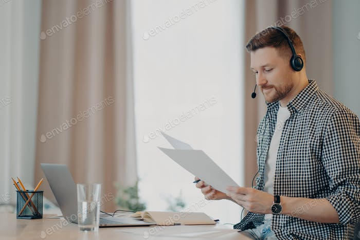 Bearded male freelancer holding documents and working remotely at home