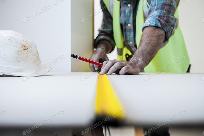 A mason takes measurements of a wooden lath.