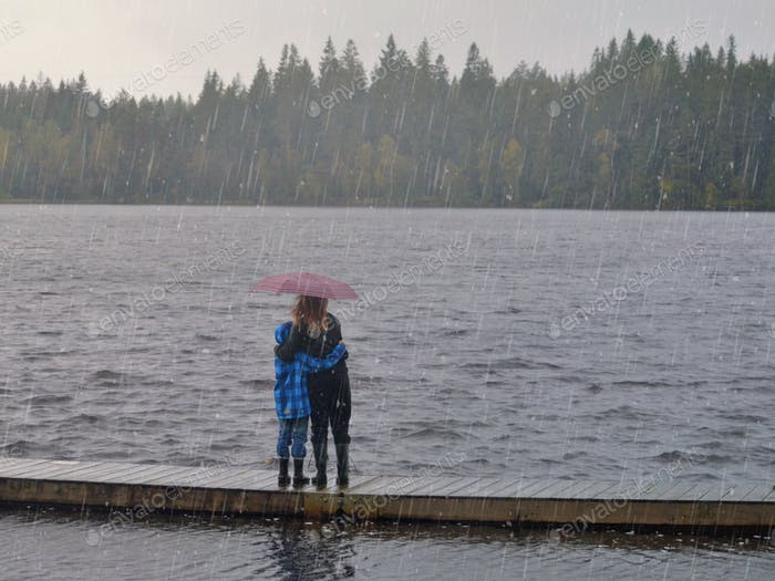 Two children on a bridge looking out on the stormy weather