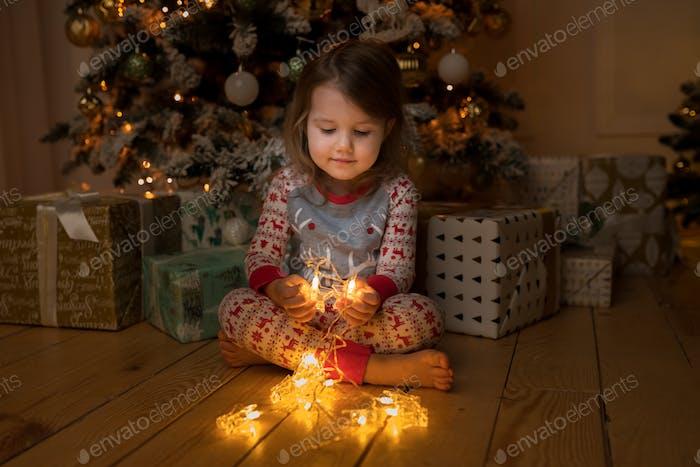 girl sitting near Christmas tree on Christmas Eve holding glowing garland
