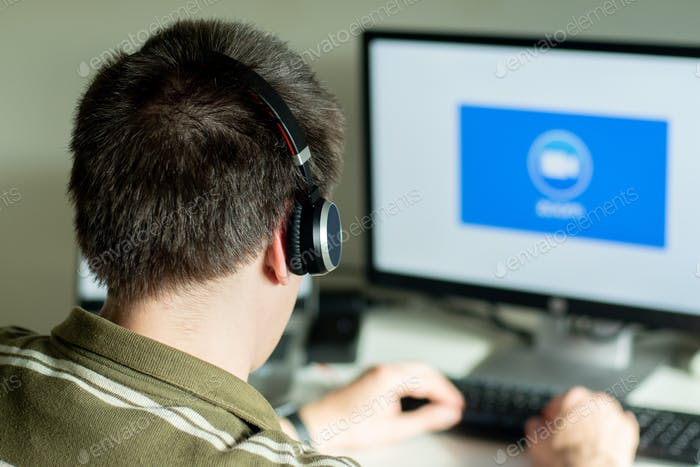 Man with headphones looking on the monitor with zoom cloud meetings logo