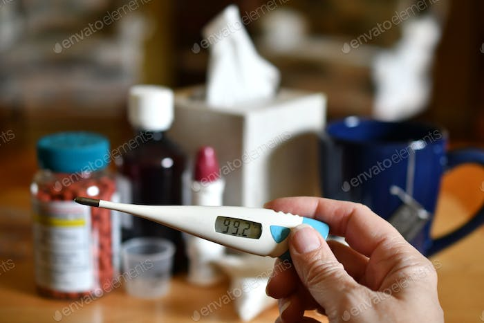 Taking my temperature with a thermometer to see if I have a fever because I feel sick with cold flu