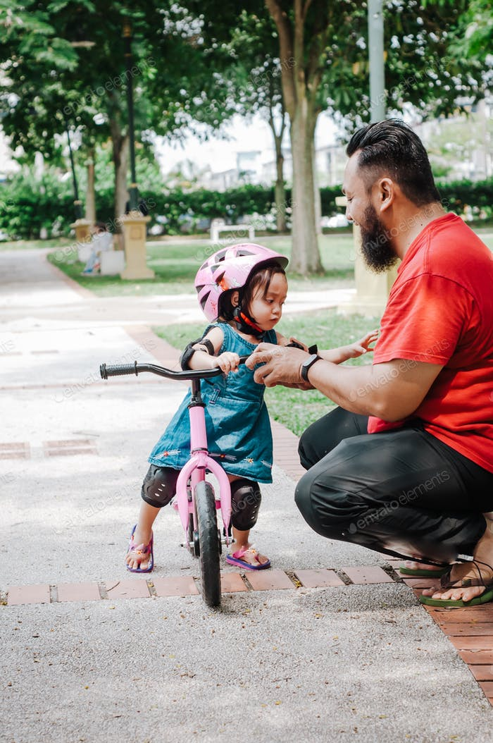 toddler girl on the push bike with father in the park