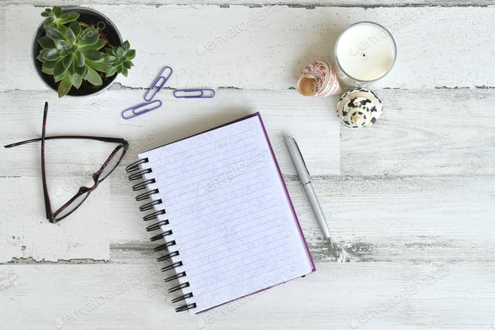 High angle view of a blank notepad journal diary on a light wooden desk or table - overhead flat lay