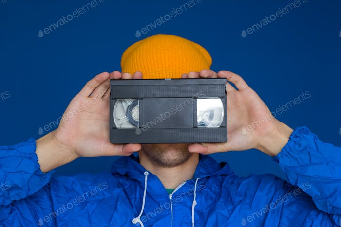 young man  in 90s sports jacket and yellow hat with VHS cassette on blue background