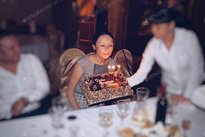 Woman blowing Birthday candles