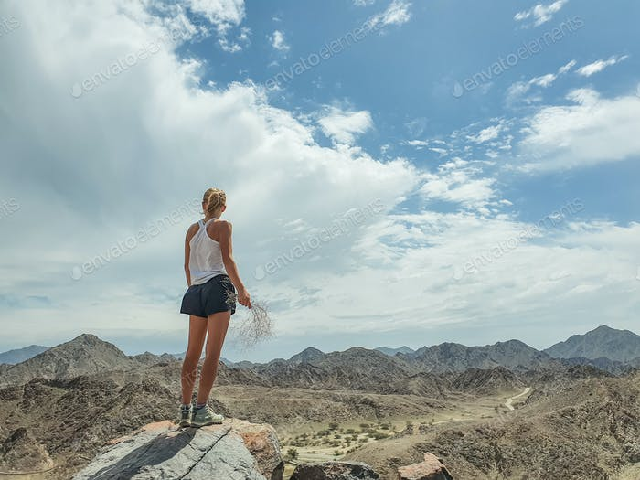 Woman standing on top of the mountain