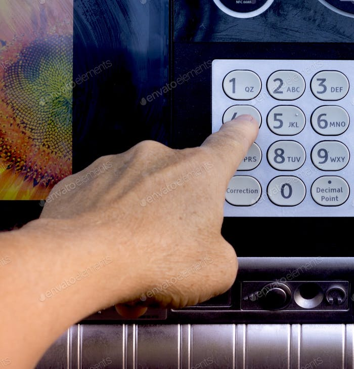 Nahaufnahme einer erwachsenen männlichen Hand mit einem Finger auf der Zifferntastatur eines automatisierten Bankautomaten, ATM.