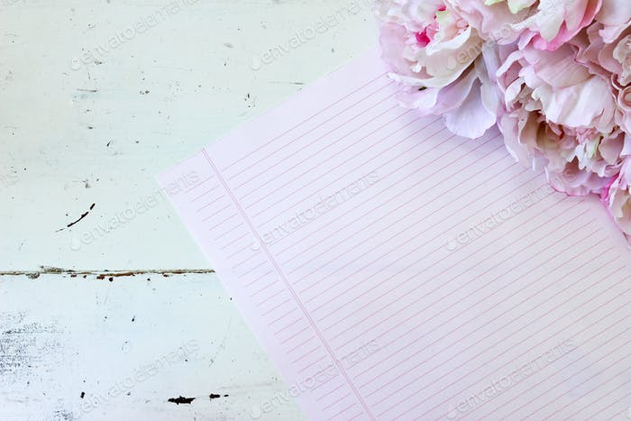 White rustic wood desk with pink notepaper and peonies