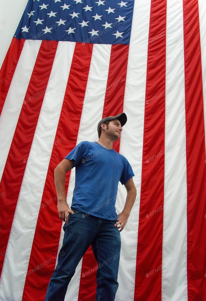 Man standing in front of United States red white and blue flag as a patriotic man