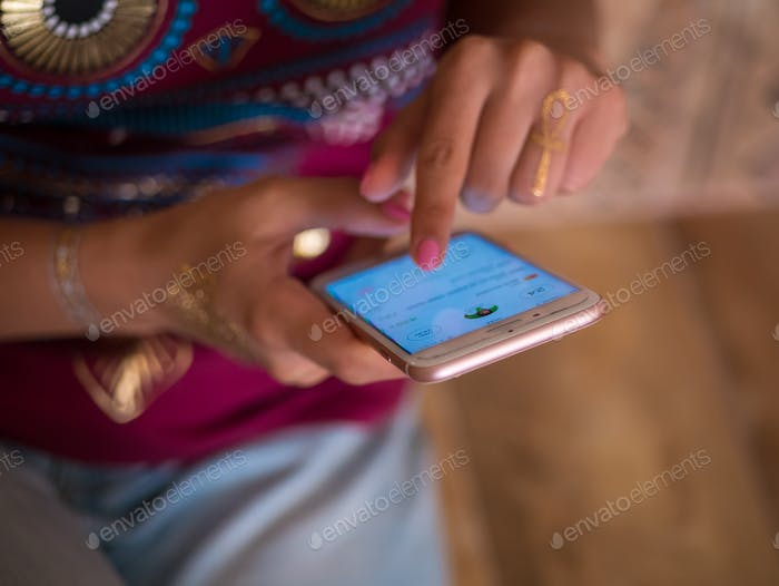 Young girl with flash tattoo on hands using smartphone
