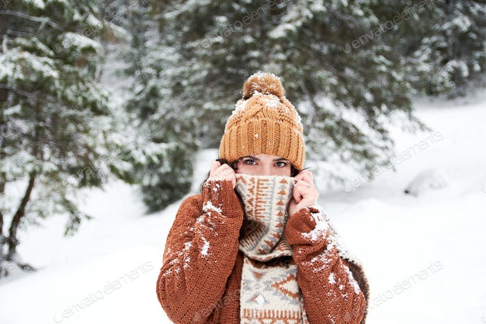 Winter portrait of a young woman. Cosy sweater covered with snow, scarf over mouth, beauty, eyes, li