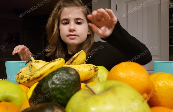 Little girl is picking fruit at the breakfast table to consume for the calories needed to get her on