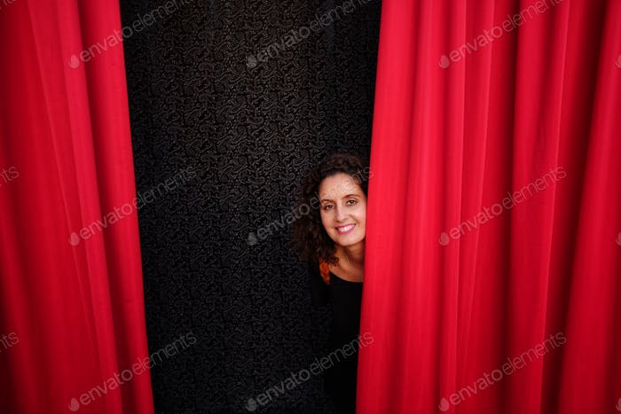 woman behind red theater curtain