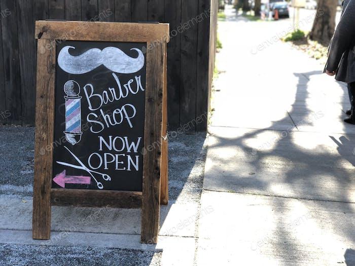 Der Friseurladen ist jetzt geöffnet. Straßen-Schild. Kreidetafel-Zeichen. Werbung, Werbung, handgezeichnet, Kunst.