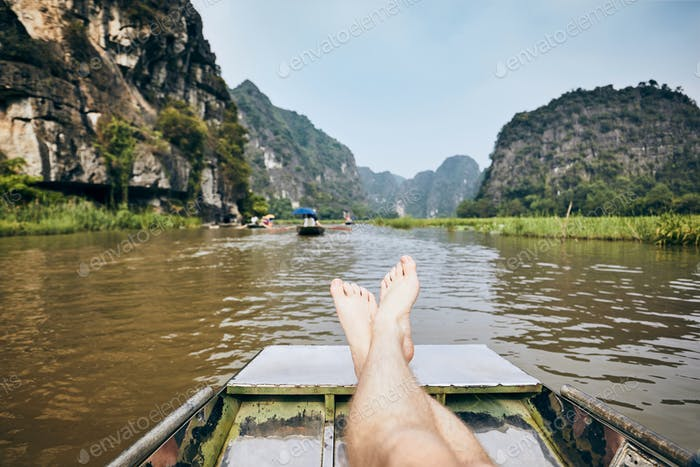 Legs of man on boat against karst formation near Tam Coc in Ninh Binh province, Vietnam