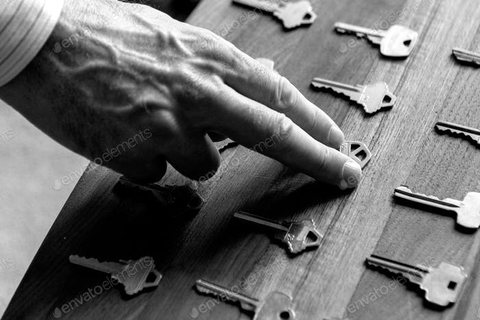 Real estate hand picking up a house key in black and white.