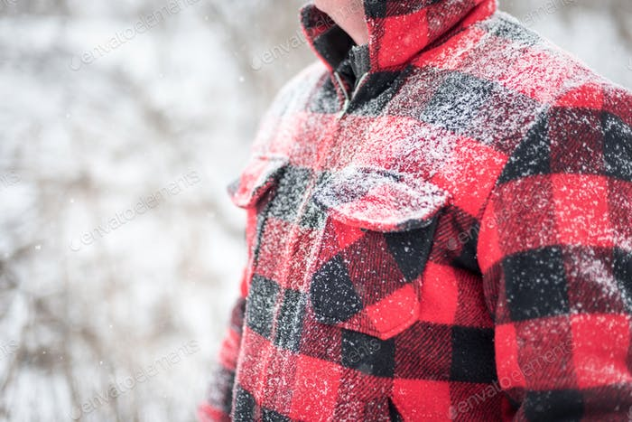 Man in red plaid wool jacket with snow covered shoulders