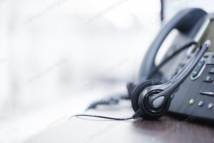 закрыть на гарнитурах карьера колл-центра с телефоном (voip) на столе Агентство поддержки