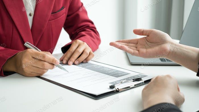 Los empresarios tienen un currículum vitae y hablan con los solicitantes de empleo para entrevistas de trabajo sobre carreras y su